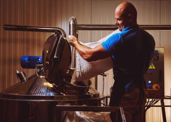 Brewer-in-brewhouse-pouring-out-the-malt-to-the-tank-1024x678